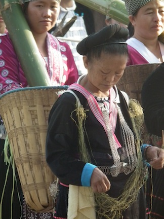 A Hmong woman doing traditional string weaving while carrying a basket on her back. She is dressed in traditional Hmong clothing.