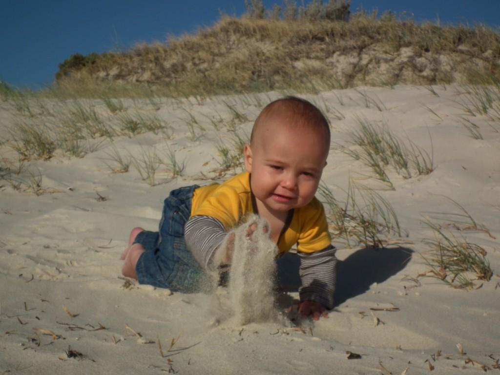 Adventuring Akiva crawling through the sand at Tennyson Dunes, South Australia