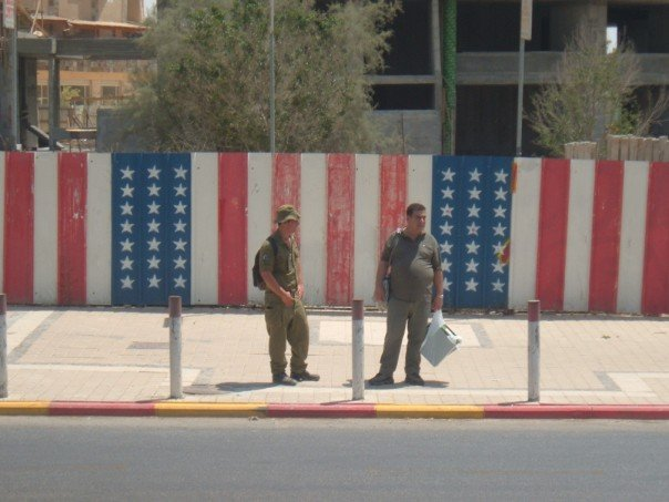 Israeli soldiers stand on a sidewalk in front of a walk painted with the American flag
