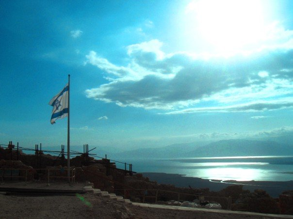 An Israeli flag flies on top of Masada, with the Dead Sea in the background