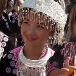 A young Hmong girl smiles in the morning sun. Her elaborate headdress and necklace is made of pure silver, which is how the Hmong people store their wealth. They do not have banks - the Hmong New Year is the only time of the year they all come out to display all their wealth.